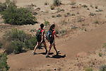 Two girls hiking in Arches National Park, Moab, Utah, USA. .  John offers private photo tours in Arches National Park and throughout Utah and Colorado. Year-round.