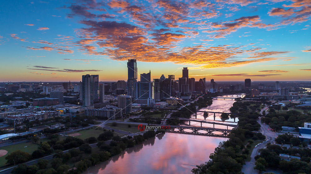 Bird's eye view of the Austin Skyline and bridges over Lady Bird Lake connecting north and South Austin during a beautiful orange sunrise