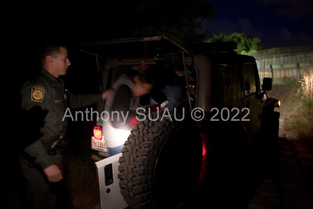 Nogales, Arizona.USA.October 24, 2006..The US border Patrol detain four Mexicans that had jumped the fence (in the back ground) from the Mexican side of Nogales to the US side.
