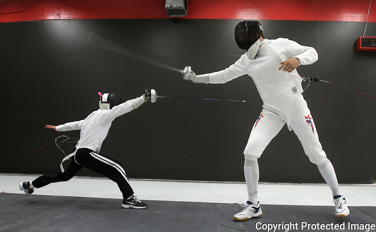 Olympic fencer Loren Thompson, right, fences with workshop attendee, Alexander Nakamura, 10, during a fencing workshop at Team Touche Fencing in Sorrento Valley in 2012.  photo for the North County TImes.