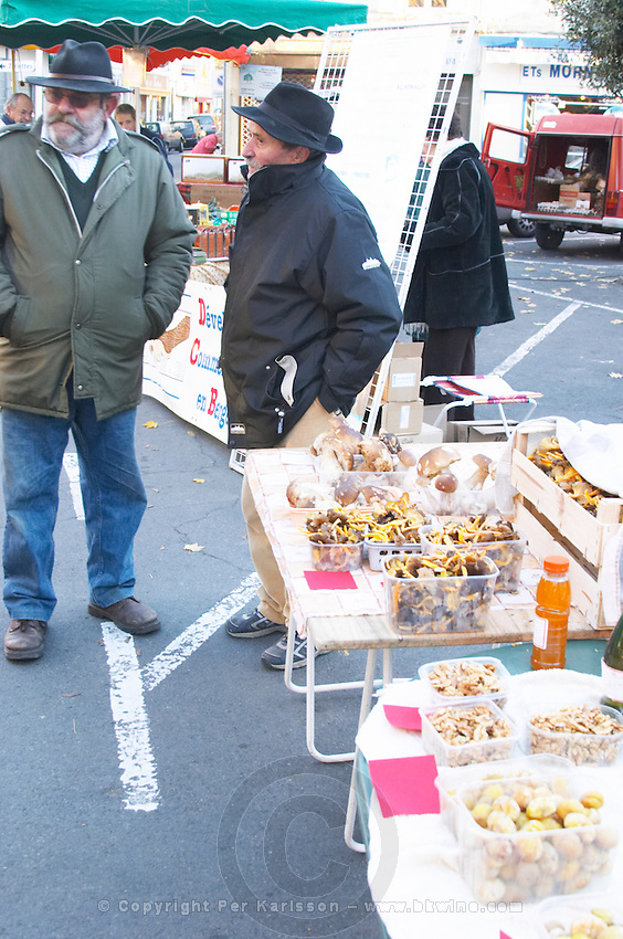 Mushrooms (porcini or cepes and chanterelles) for sale at a market stall at the market in Bergerac. Two men in hats selling their products. Bergerac Dordogne France
