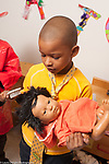 Education preschool pretend play boy wearing tie brushing doll's hair with small brush, wearing dressup tie