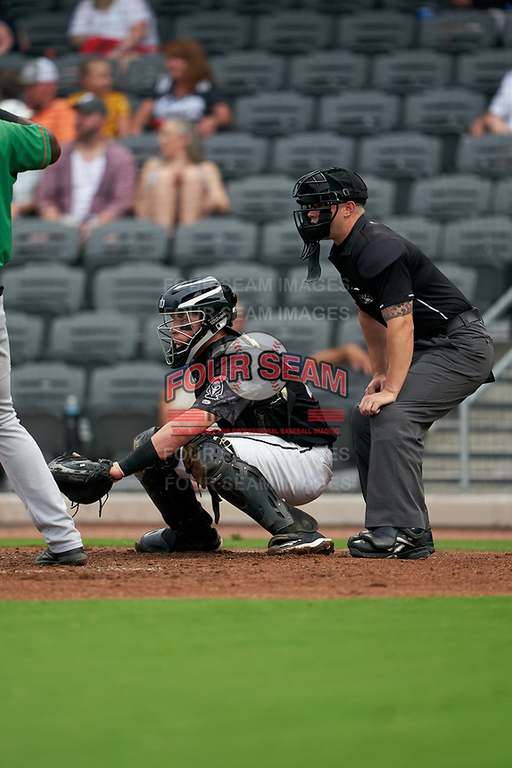 Fayetteville Woodpeckers catcher Michael Papierski (28) and umpire Mark Bass during a Carolina League game against the Down East Wood Ducks on August 13, 2019 at SEGRA Stadium in Fayetteville, North Carolina.  Fayetteville defeated Down East 5-3.  (Mike Janes/Four Seam Images)