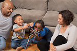 Family at home playing game with balancing metal rods, girl age 10, boy age 5