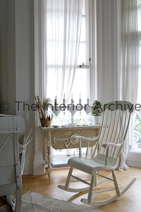 A white rocking chair and a marble topped console table beside the floor-to-ceiling windows of the living room