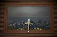 Grand Tetons National Park is reflected through the Chapel of Transfiguration on November 11, 2009.