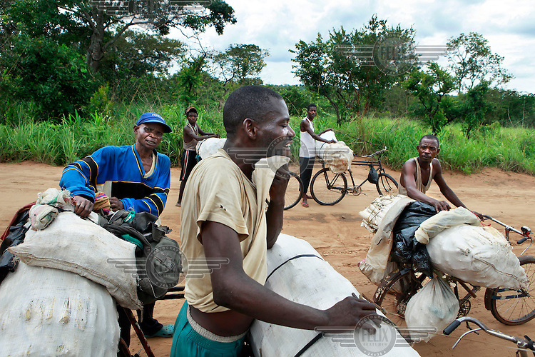 A group of farmers transport some of their produce by bicycle along an unpaved road.