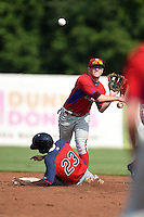 Andrew Noviello (15) of Bridgewater-Raynham Regional High School in Raynham, Massachusetts playing for the Philadelphia Phillies scout team attempts to turn a double play as Xavier LeGrant (23) slides in during the East Coast Pro Showcase on August 1, 2014 at NBT Bank Stadium in Syracuse, New York.  (Mike Janes/Four Seam Images)