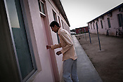 25 year old Chinese interpreter, Yuan Lei walks into his dormitory of the Chinese Colony in the Adani Power plant in Mundra port industrial city of Gujarat, India. Indian power companies have handed out dozens of major contracts to Chinese firms since 2008. Adani Power Ltd have built elaborate Chinatowns to accommodate Chinese workers, complete with Chinese chefs, ping pong tables and Chinese television. Chinese companies now supply equipment for about 25% of the 80,000 megawatts in new capacity.
