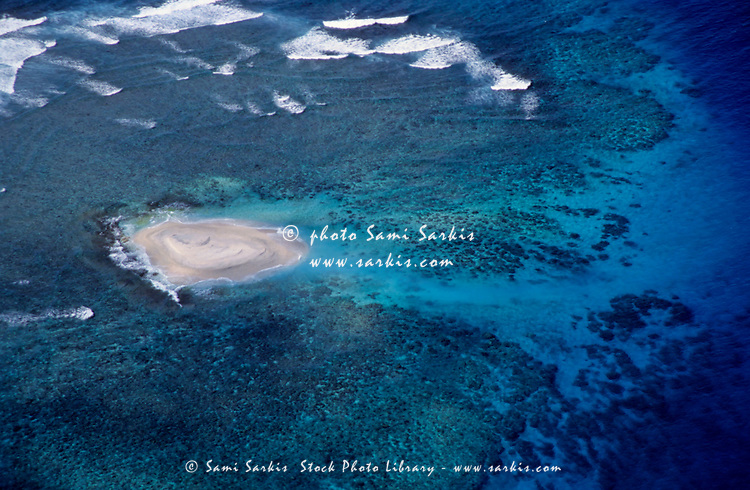 Sandy island surrounded by tropical seas in the Pacific Ocean.