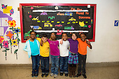 "MR / Schenectady, New York. Yates Arts-in-Education Magnet School (urban public school). First grade classroom. Group portrait of first-grade classmates in front of bulletin board with the theme of ""on the road to success"".  MR: AM-g1w. ID: AM-g1w. © Ellen B. Senisi."