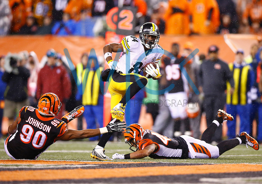 Antonio Brown #84 of the Pittsburgh Steelers evades a tackle from Michael Johnson #90 of the Cincinnati Bengals  after catching a pass in the second half during the Wild Card playoff game at Paul Brown Stadium on January 9, 2016 in Cincinnati, Ohio. (Photo by Jared Wickerham/DKPittsburghSports)