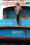 Large passenger ferries ply the many waterways in Bangladesh. Here a man has a refreshing bucket wash on a rear platform of a moored ferry.
