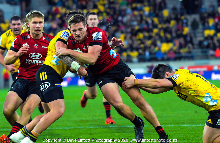 Hurricanes captain TJ Perenara tackles Crusaders' George Bridge during the Super Rugby Aotearoa match between the Hurricanes and Crusaders at Sky Stadium in Wellington, New Zealand on Saturday, 21 June 2020. Photo: Dave Lintott / lintottphoto.co.nz
