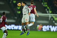 Virgil van Dijk jumps with Andy Carroll of West Ham United during West Ham United vs Liverpool, Premier League Football at The London Stadium on 4th February 2019