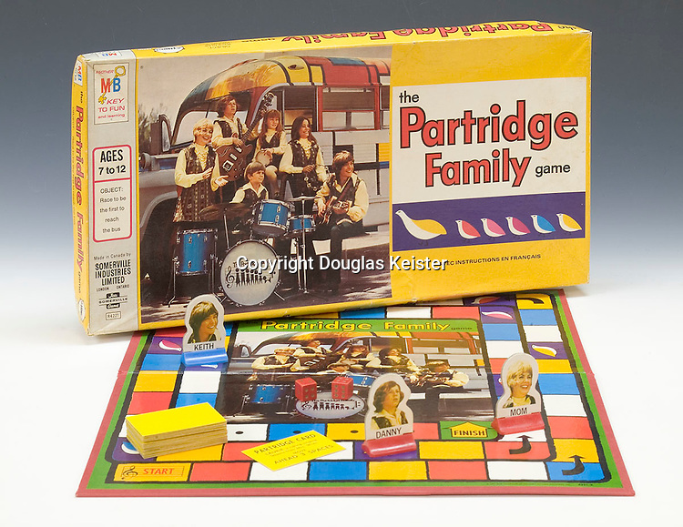 """The Partridge Family, a sitcom that featured a widowed mother and her five children that aired on ABC Television from 1970 until 1974, had its own version of a brightly painted hippie bus. Appropriately the bus was painted in a more geometric (square) pattern than the free-flowing designs of the hippie buses. In the series, the Partridge family acquired a 1957 Chevrolet school bus from Al's Used Cars because they needed a vehicle to transport them and their equipment to a gig at Caesar's Palace in Las Vegas. The family painted the bus in a geometric-style reminiscent of Dutch painter Piet Mondrian, and they were on their way. <br /><br />After the show's demise, the bus went through a series of owners and eventually wound up lame and abandoned in the parking lot of Lucy's Tacos in east Los Angeles. A short time later, it was junked. When David Cassidy, who played Keith Partridge on the original series, went on a revival tour in 1993, he traveled in a look-alike bus. Another copy of the original bus can be seen at Universal Studios in Florida. For the Partridge-trivia minded, the rear of the bus sported license plate number NLX 590 and a sign that read, """"Careful, Nervous Mother Driving."""" <br /><br />The Partridge Family series generated a number of spin-off products, including records, refrigerator magnets, lunch boxes, books, posters, and games. In The Partridge Family Game, each roll of the dice can potentially put a family on their way to getting on the bus and winning the game, or could make the family land on one of the birds and be subject to drawing a card that could put them in peril. For reasons known only to the game's inventor, drawing a Partridge card that says, """"LAURIE belongs to the 'now generation',"""" causes the contestant to lose a turn while drawing a card that says, """"MOM likes to sing in the shower,"""" advances the player six spaces."""