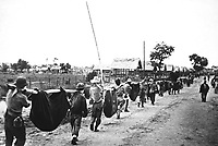 This picture, captured from the Japanese, shows American prisoners using improvised litters to carry those of their comrades who, from the lack of food or water on the march from Bataan, fell along the road.  Philippines, May 1942. (OWI)<br /> Exact Date Shot Unknown<br /> NARA FILE #:  208-AA-288BB-2<br /> WAR & CONFLICT BOOK #:  1145