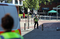 Pictured: Police in Oxford Street in Swansea city centre with the entrance to the Quadrant in the background Wednesday 24 May 2017<br />Re: The Quadrant shopping centre in Swansea has been evacuated following reports of a suspicious package being found.<br />The bus station and Swansea Indoor Market have also been closed as part of the evacuation.