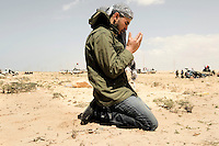 A man prays as he joins the front at Ajdabiya. On 17 February 2011 Libya saw the beginnings of a revolution against the 41 year regime of Col Muammar Gaddafi.