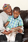 father at home with 3 year old son sitting on couch reading to him from illustrated book about rocks gems and minerals vertical