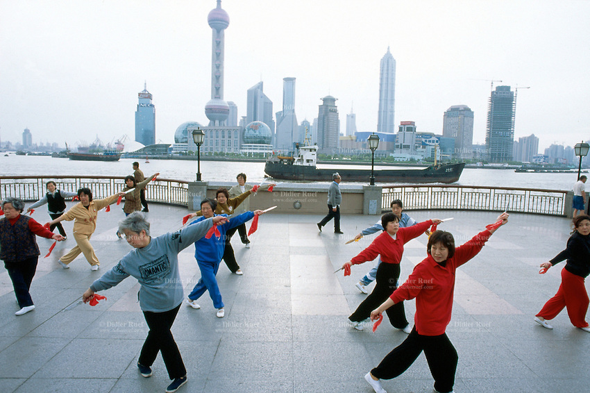 """China. Shanghai. Downtown. City center. Pudong skyline seen from """"The Bund"""". Early morning a group of chinese  women are doing their daily exercices. They dance with swords and knifes. Over 1 and 1/2 times larger than urban Shanghai itself, the Pudong new area consists of the entire eastern bank of the Huangpu river. Pudong is the new area of development where the growing business needs constantly new modern high buildings, real """"skyscrapers"""". Pudong has become Shanghai and China's economic powerhouse.The Bund is the most impressive 2 km in Shanghai. © 2002 Didier Ruef"""