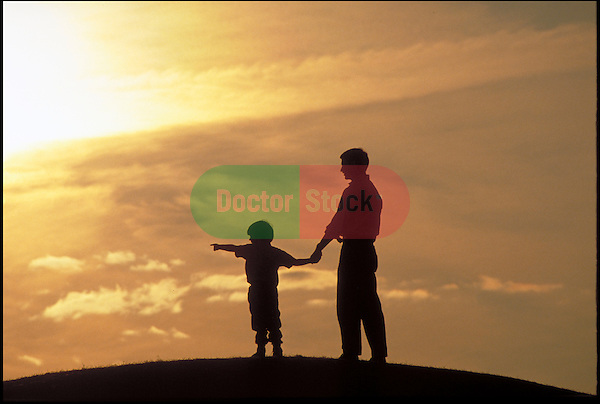 silhouette of father and child with sunset