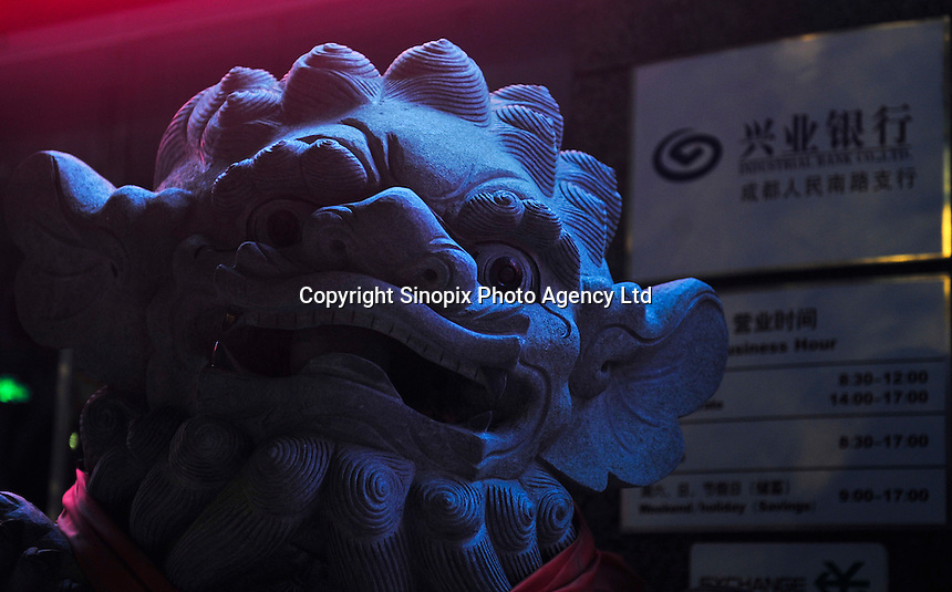 A large stone lion sculpture placed in front of a Industrial Bank Co. Ltd., Chengdu, China. A pair of carved stone lions stand outside the entrance of the bank are believed can guard the bank and also keep the bad spirit away..