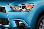 Driver side front headlight detail view of a Angular close up detail of the grille on a 2011 Mitsubishi Outlander Sport SE
