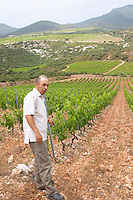 Sylvain Fadat Domaine d'Aupilhac. Montpeyroux. Languedoc. Les Cocalieres recently planted magnificent vineyard plot on the hill slope. Terroir soil. Owner winemaker. France. Europe. Vineyard. Mountains in the background. Soil with stones rocks.
