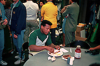 OAKLAND, CA - Rickey Henderson of the of the Oakland Athletics eats ribs from the spread in the A's clubhouse after a game against the Seattle Mariners at the Oakland Coliseum in Oakland, California on August 12, 1994. The baseball strike went into effect as this game ended. (Photo by Brad Mangin)