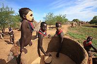 In the village of Korcho on the Omo River, the women open a loft to get out some sorghum. The Karos have become a sedentary people, settled on the banks of the Omo, following the loss of all their animals due to an epidemic of bovine plague. They have reconstituted only a part of their livestock; they live from subsistence farming, taking advantage of rises in the river's water level. ///Village de Korcho sur le fleuve Omo, les femmes Karas ouvrent un grenier pour y prélever du sorgho. Les Karos se sont sédentarisés sur les berges de l'Omo après la perte de toutes leurs bêtes suite à une épidémie de peste bovine et ils ont reconstitué en partie seulement leur cheptel. Ils vivent d'agriculture de subsistance en profitant des crues de la rivière.