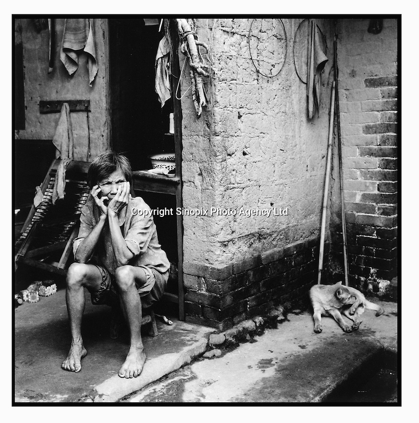 Wei Cai Xiang (69), the wife of Zhu Geng Wu, sits in her traditional home during the hot mid-day hours before heading out to the fields for a second time until evening closes in. The poverty gap in China is a major theme at this years National People's Congress in Beijing since it is causing destabilization of the country as farmers sick of corrupt official take matters into their own hands...PHOTO BY SINOPIX