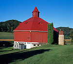 Pepin County, WI<br /> Octagonal red barn in a summer valley beneath a wooded hillside