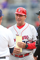 Spokane Indians Manager Tim Hulett (36) gives his lineup card to the umpires before a game against the Everett AquaSox at Everett Memorial Stadium on July 24, 2015 in Everett, Washington. Everett defeated Spokane, 8-6. (Larry Goren/Four Seam Images)