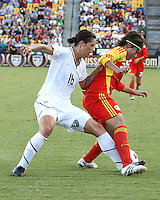 Ali Krieger #16 of the USA WNT pokes the ball away from Yasha Gu #24 of the PRC WNT during an international friendly match at KSU Soccer Stadium, on October 2 2010 in Kennesaw, Georgia. USA won 2-1.