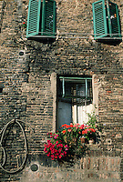 The brick exterior facade of an old building with flowers in the window and colorful shutters above. Siena, Italy.