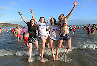 Pictured: Four young women jump in the freezing cold sea in Tenby, west Wales, UK. Monday 26 December 2016<br /> Re: Hundreds of people in fancy dress, take part in this year's music-themed charity event, the Boxing Day Swim in Tenby, Pembrokeshire, Wales, UK