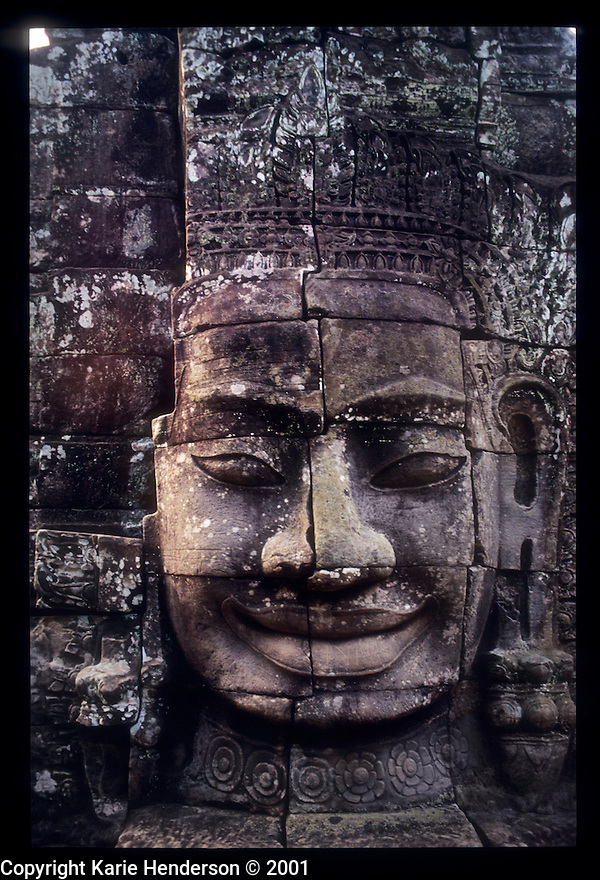 A carved stone Buddhist trinity head outside of Wat Bayon, in Siem Reap, Cambodia.  Photo by, Karie Henderson © 2001