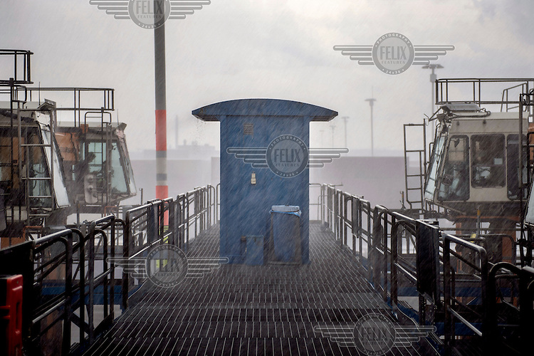 The straddle carrier station during a storm. Straddle carriers are very high vehicles that carry the containers to the ship ready for loading.