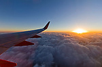 Sunrise over the clouds while flying high on SouthWest Airlines after takeoff