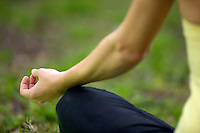 closeup of woman's hand resting on her leg while she meditates outdoors in a field