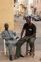 Senegal, Saint Louis. Two Senegalese Men Relaxing on a Street Corner.  The one on the right, in western-style clothes, is a photographer.