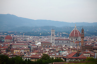 Firenze: A panoramic view with a part of the historical center in foreground. The photo is taken form the top of a hill nearby, and one can distinguish various landmarks of the town, among which dominate the ancient cathedral of Santa Maria del Fiore, and the ancient Palazzo Vecchio with its characteristic  tower (on the right), whereas one can see the main dome of the church of San Lorenzo, too (on the left).