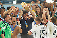 Germany manager Joachim Low lifts the World Cup trophy after winning the 2014 final celebrating with his players