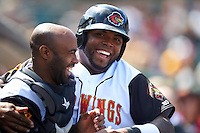 Rochester Red Wings designated hitter Kennys Vargas (35) and catcher Carlos Paulino (17) celebrate in the dugout after a run during a game against the Toledo Mudhens on June 12, 2016 at Frontier Field in Rochester, New York.  Rochester defeated Toledo 9-7.  (Mike Janes/Four Seam Images)