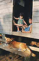 Philippines. Negros Island. Province of Negros Occidental, located in the  Western Visayas region. Barangay (village) Camao. Two young children, brother and sister, and a dog on the doorstep of a wood house. © 1999 Didier Ruef