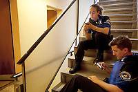 Switzerland. Geneva. Paquis neighborhood. Two police officers seat on the staircase of a building's hallway. Both are waiting for a locksmith to arrive and close the door of a flat which was burglarised. The policeman and the policewoman are playing with their iphones. They are wearing a ballistic vest, bulletproof vest or bullet-resistant vest which is an item of personal armor that helps absorb the impact from knives, firearm-fired projectiles and shrapnel from explosions, and is worn on the torso. Soft vests are made from many layers of woven or laminated fibers and can be capable of protecting the wearer from small-caliber handgun and shotgun projectiles, and small fragments from explosives such as hand grenades. 25.07.12 © 2012 Didier Ruef..