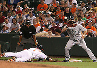 Casey Kotchman #13 of the Seattle Mariners trys to get Brian Roberts #1 of the Baltimore Orioles out at first during a MLB game at Camden Yards, on August 8 2010, in Baltimore, Maryland. Orioles won 5-4 in extra innings.