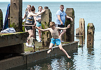 UK Weather: Aberystwyth, Ceredigion, West Wales. Youngsters jump off a platform as people are out in force today taking full advantage of the summer heat, with temperatures of 23 in town. With temperatures reportedly hitting 25 in other parts of the United Kingdom.