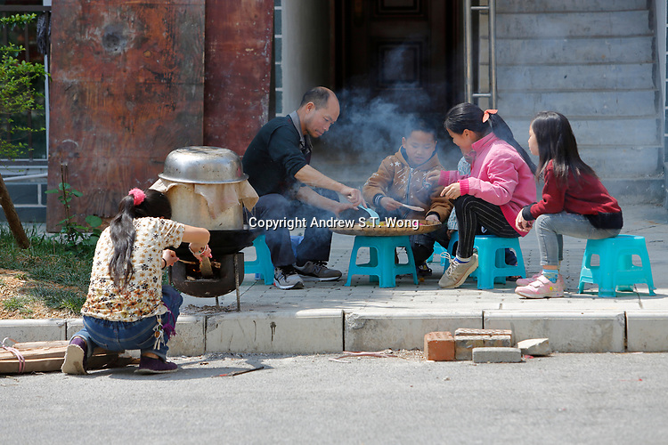 A family cooks traditional coloured sticky rice at Wangmo County in China's southwestern Guizhou Province, April 2019.